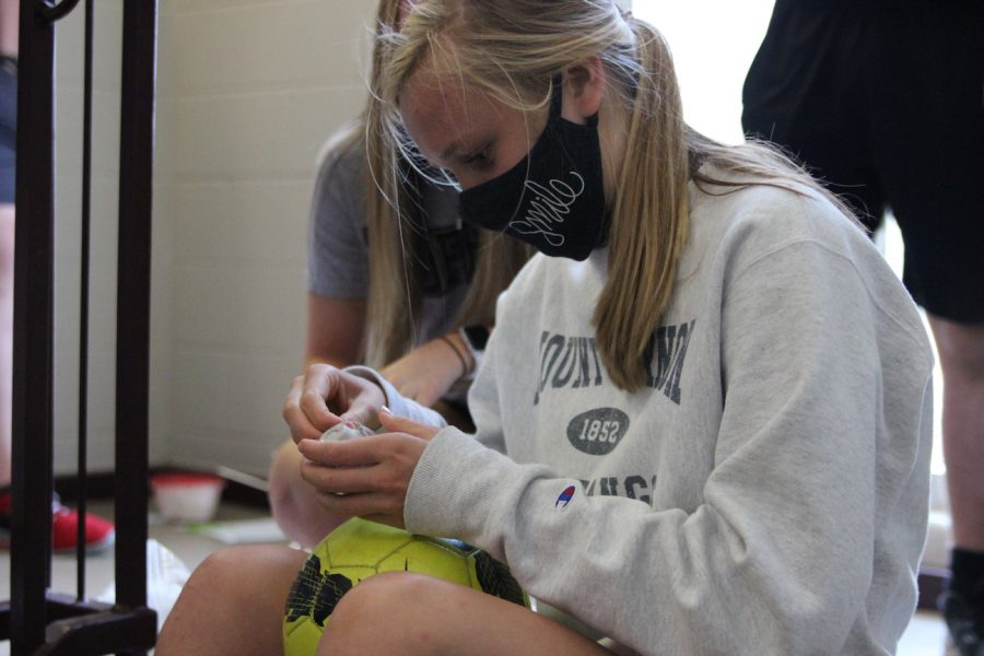 Junior Anna Hoffman checks her egg after the egg drop in Physics Sept. 17. Hoffman's egg was one of only a few eggs that survived the drop from the top of the stairwell. Hoffman put her egg in a hollowed-out soccer ball filled with protective materials for the drop.