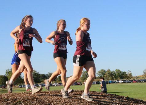 Juniors Quinlan Denes and Lillian Booth and senior Elizabeth Niehaus run together at the Iowa City Regina Meet Sept. 3. Both the boys