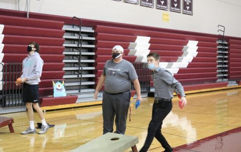 Students play bags at the Halloweentown homecoming party Oct. 10.