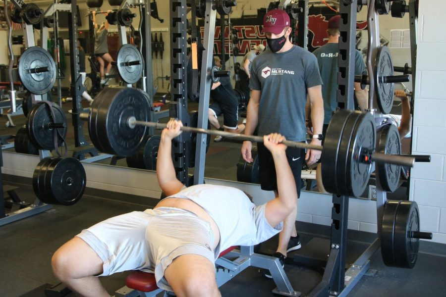 Physical Education teacher Preston Pedersen spots for a weightlifter Nov. 13.