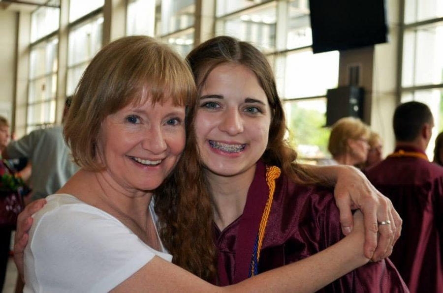 Spanish teacher Sue Deibner gives 2013 graduate Alexis Bell a hug.