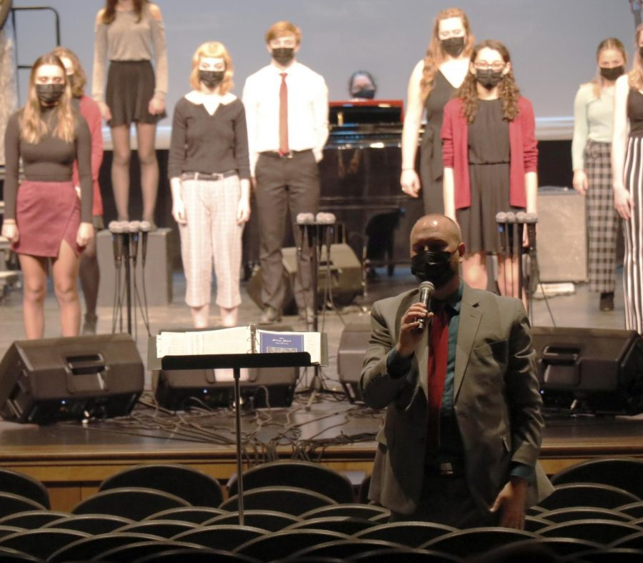Director, Thad Wilkins, informs audience about the music concert choir sings and speaks proudly of his students.