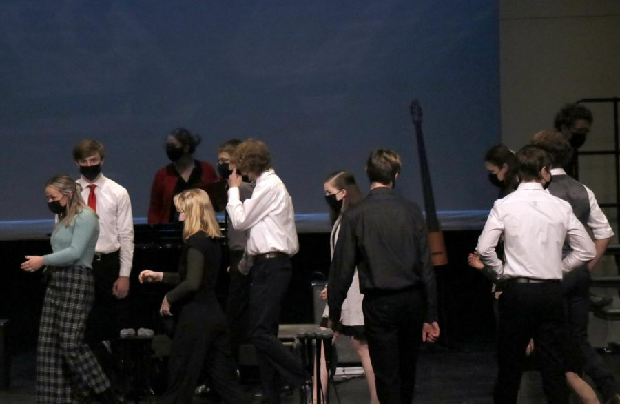 Singers from concert choir leave stage and acknowledge each other after their performance.