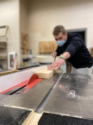 Senior, Connor Klinkhammer, is slicing his other board using the table saw without a guard.