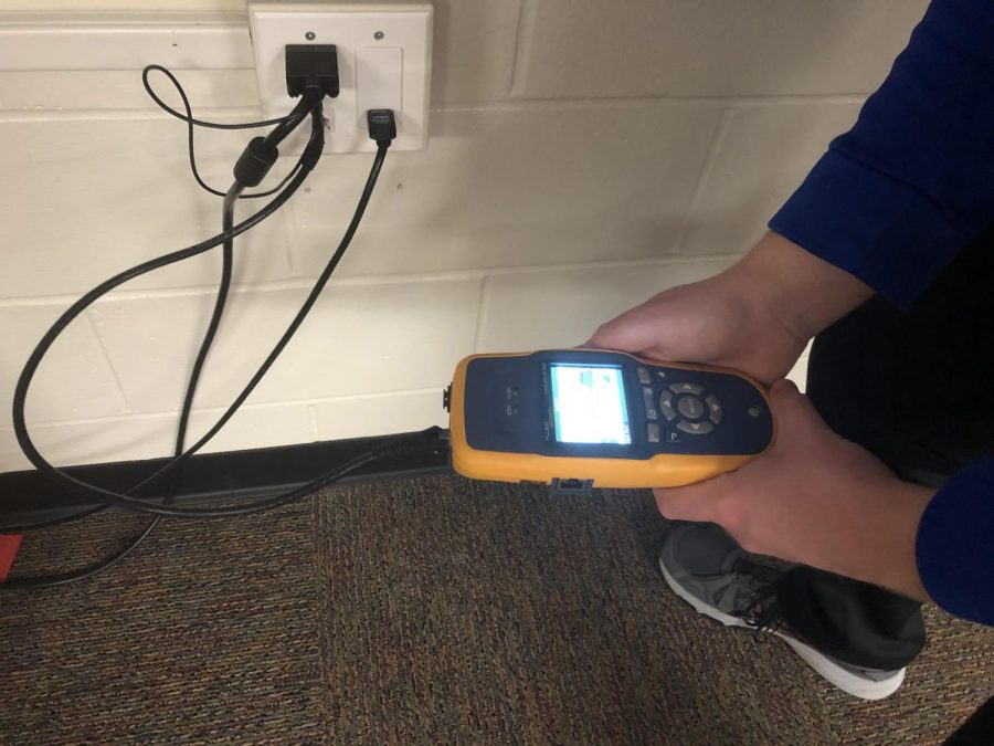 It was vital for the team to finish the project before students returned from winter vacation. As the team of two walked from room to room, they ran an ethernet cable from each wall to the network tester. The bright screen of the tester sparked to life in the quiet, empty classrooms.