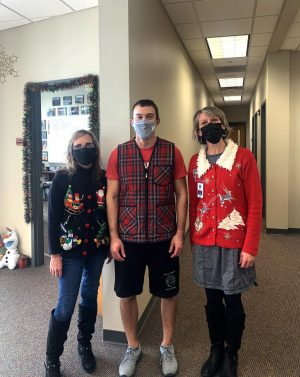 Office workers Mary Hale, Stephanie Timm, and Gym teacher Ryan Whitman pose for a picture in their holiday attire.