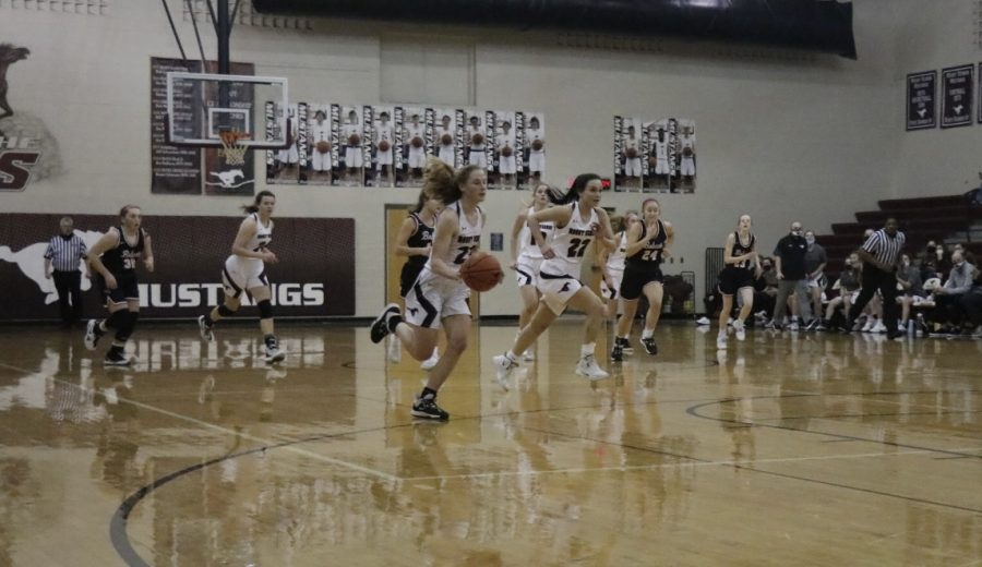M.V. Mustangs hustle down the court while Lily See dribbles the ball Feb. 2.
