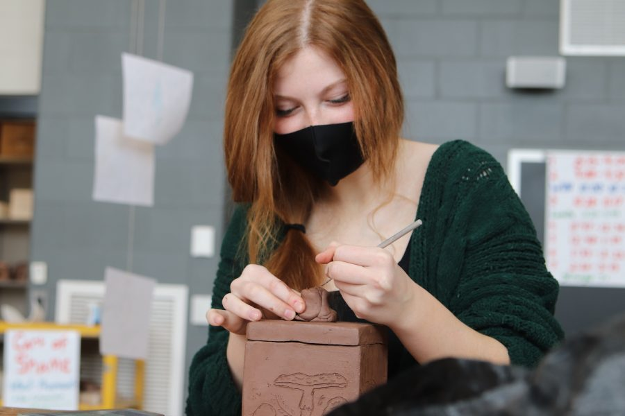 Molding the clay into a knob for her box, sophomore Laila Moellering puts the finishing touches on her project in Ceramics Feb. 3. Moellering etched designs onto the faces of her box. One face depicted a mushroom and Moelllering planned on making the knob on top of her box a mushroom as well.