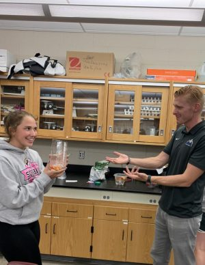 Sophomore Kenna Rollinger presents her biogoly project to science and math teacher Derek Roberts who commends her work.