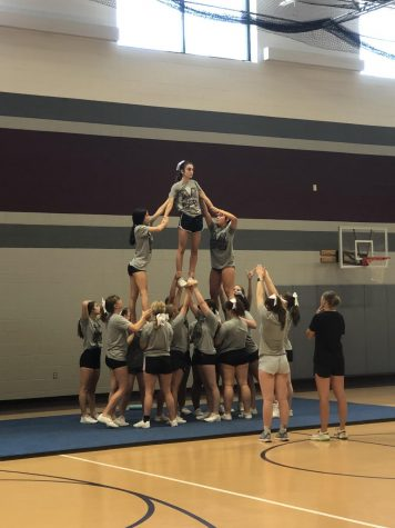 Flyer, Kambree Hultquist, practices a pyramid with the help of multiple teammates Aug. 28.