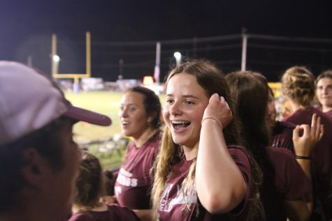 """Junior Isabel Hawker laughs after senior Aden Locke spells """"Squid"""" wrong, leading a cheer for football player Austin (Squid) Deeb."""