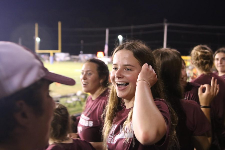 Junior Isabel Hawker laughs after senior Aden Locke spells Squid wrong, leading a cheer for football player Austin (Squid) Deeb.