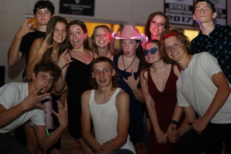 A group of students pose for a picture on the dance floor.